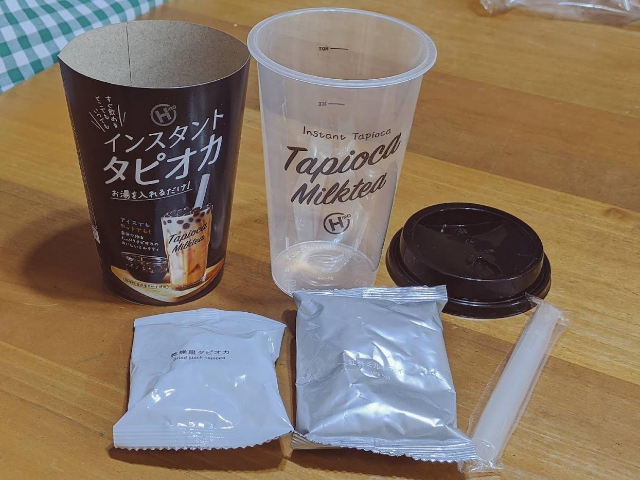 インスタントタピオカ開封した画像 手前にタピオカと粉末ミルクティー1袋ずつ、後ろにラベルと空のカップ、ストロー
