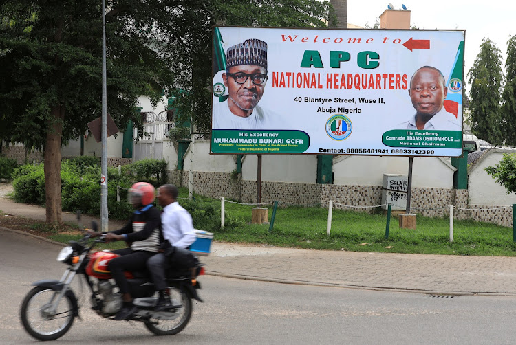 Men on a motorbike ride past a sign for the All Progressive Congress (APC) national headquarters in Abuja, Nigeria on July 5, 2018.