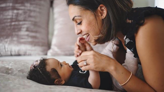 Mujer sonriendo a recién nacido con mameluco negro y sosteniendo las manos del bebé.