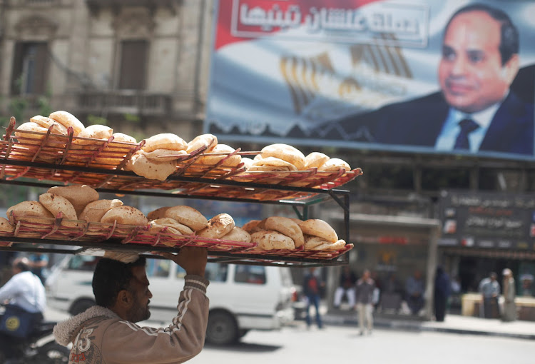 A man carries breads on his head along a busy street near a banner for Egypt's President Abdel Fattah al-Sisi after election results in Cairo, Egypt April 3, 2018.