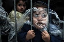 angstig kijkende vrouw, met stuk plastic voor het gezicht, houdt spijlen van een hek vast