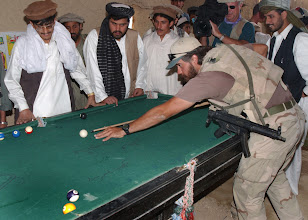 Photo: An unidentified US Army (USA) Special Forces Soldier, armed with a Heckler and Koch 9mm MP5A3 sub-machine gun, plays a game of pool with local Afghani teens in a small village in Afghanistan, during Operation ENDURING FREEDOM.