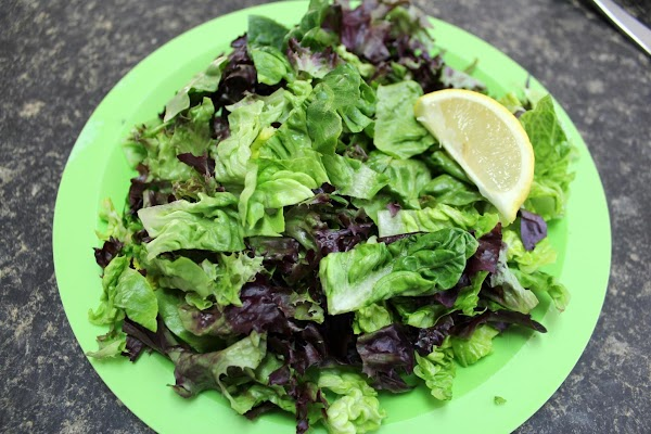 Toss the salad greens with the one half tablespoon of olive oil and the...