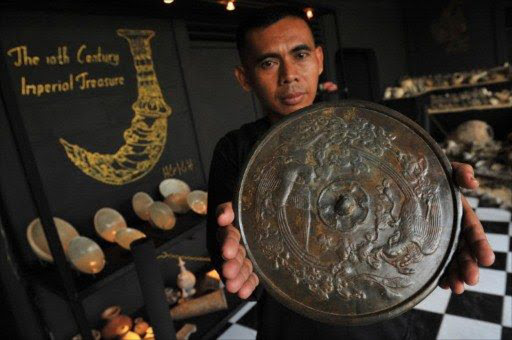 A man holds a 10th century Chinese bronze mirror plate from the Five Dynasties (907-960) at a showroom in south Jakarta. File picture
