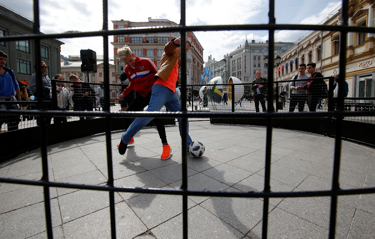 Youths play with a ball on the first day of the 2018 Fifa World Cup in central Moscow, Russia. Picture: REUTERS/SERGEI KARPUKHIN