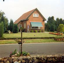 Photo: Keukenhof 13: Trientje van Jan Hadderingh voor haar huis. Het is tentoonstelling, de vlag gaat uit.