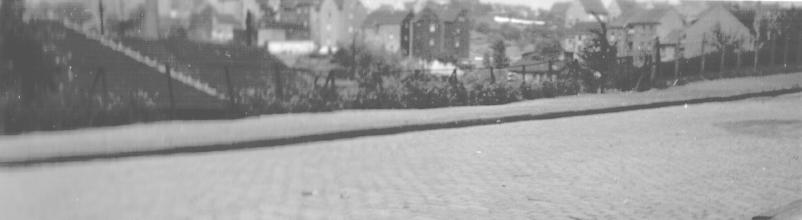 Photo: Der Standort des Photographen (wohl Wilhelm Rothe junior) ist mir nicht bekannt; vermutlich befindet sich im Hintergrund der seichte untere Volmehang nördlich von Altenhagen. Bei dem Gebäudedach links könnte es sich um eine Fabrik (Ziegelei?) oder um einen Lokschuppen handeln; bei dem Fleck am rechten Bildrand (auf der Straße) liegt der Gedanke an einen verfüllten Bombentrichter nahe. Möglicherweise handelt es sich bei der gepflasterten Straße um eine Brückenauffahrt.