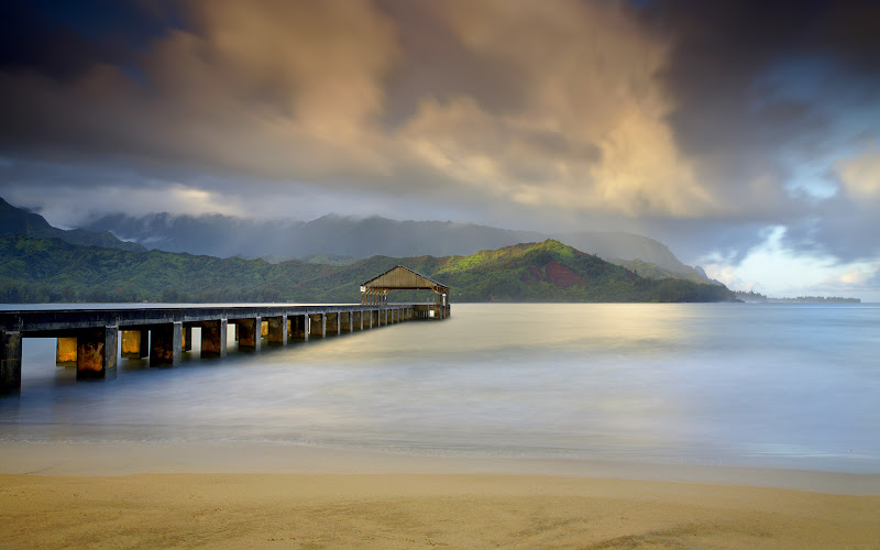"Photo: The Hanalei Pier points directly towards the mountains often referred to as ""Bali Hai.""   It refers to a song written by Richard Rodgers and Oscar Hammerstein II from the musical South Pacific. This area resembles the island of Tioman, which is the original Bali Hai.  With the sun rising behind the camera, openings in the clouds allowed the light to filter into the clouds and illuminate the mountains on the opposite side of Hanalei Bay.  Within 10 minutes the rain came in and this low warm light was gone for the day, replaced later by the bright light of mid-day.   I used a long exposure to show the motion in the clouds.  Also, the long exposure time smoothed out the water and simplified the image.  That enhanced the effect of light hitting the posts of the pier."