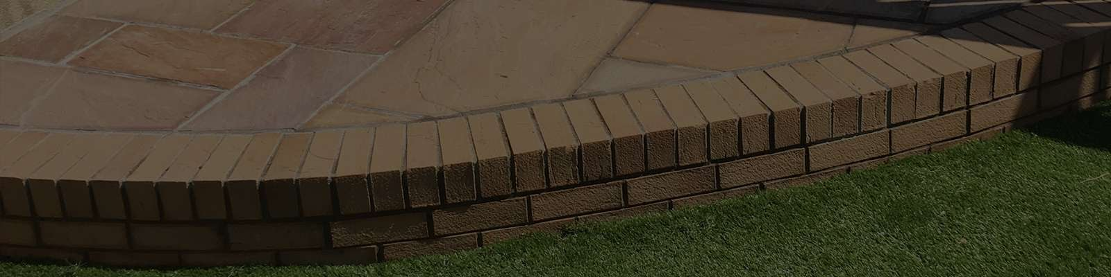 a garden patio made with brick and brick tiles