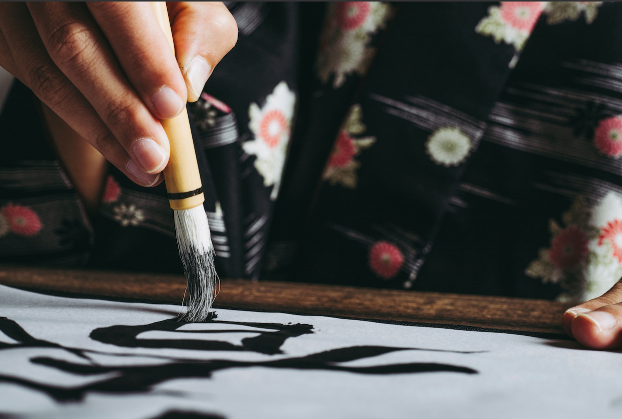 Woman writing Japanese with a traditional equipment which is a brush.