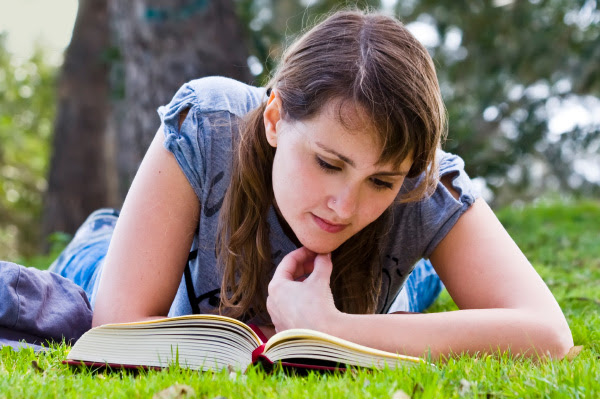 woman reading a book outside on the grass