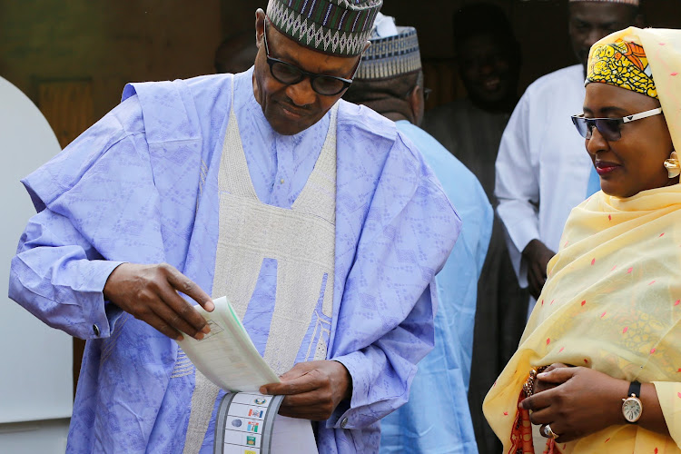 Nigerian President Muhammadu Buhari, accompanied by his wife Aisha Buhari casts his vote in Nigeria's presidential election at a polling station in Daura, Katsina State, Nigeria, February 23, 2019.