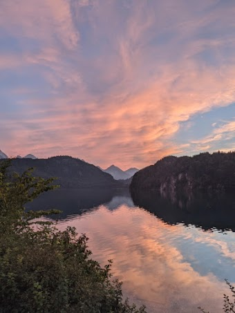 Beautiful mountain scene showing a clear lake reflecting a cloudy sunset-lit sky. Captured on Pixel.