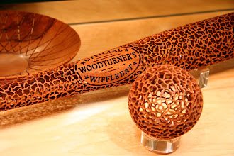 """Photo: Wifflebat (detail) and ball by J. Paul Fennell in front of Harvey Fein bowl. The turners comments: The bat is made in three 10"""" sections that are sleeved together. Each section was hollowed out--the middle one was challenging because of the two open ends. The end of the bat was also challenging because it required hollowing a thin """"tube"""" 10"""" deep. I made the billets from mesquite that was recently cut down and very wet. As a tribute to just how stable this wood is, there was no distorion when I sleeved and glued everything together after hollowing. The ball was made from one piece, turned on several axes in a jam chuck, as Christian Burchard would do. Small holes were drilled on the axes to hollow the inside, again in a jam chuck."""