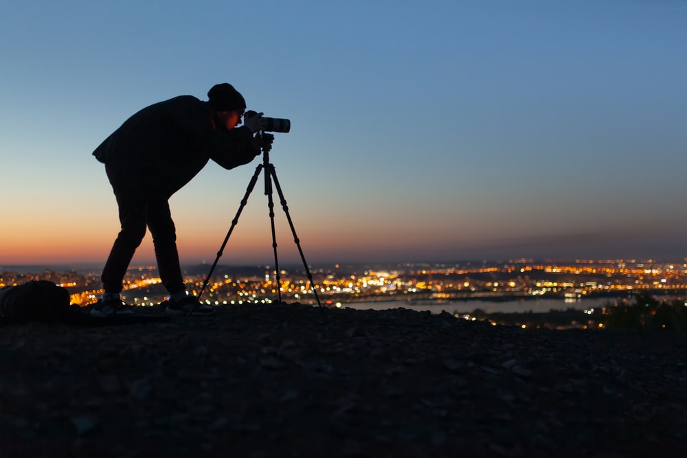 silhouette of man holding camera on tripod during sunset
