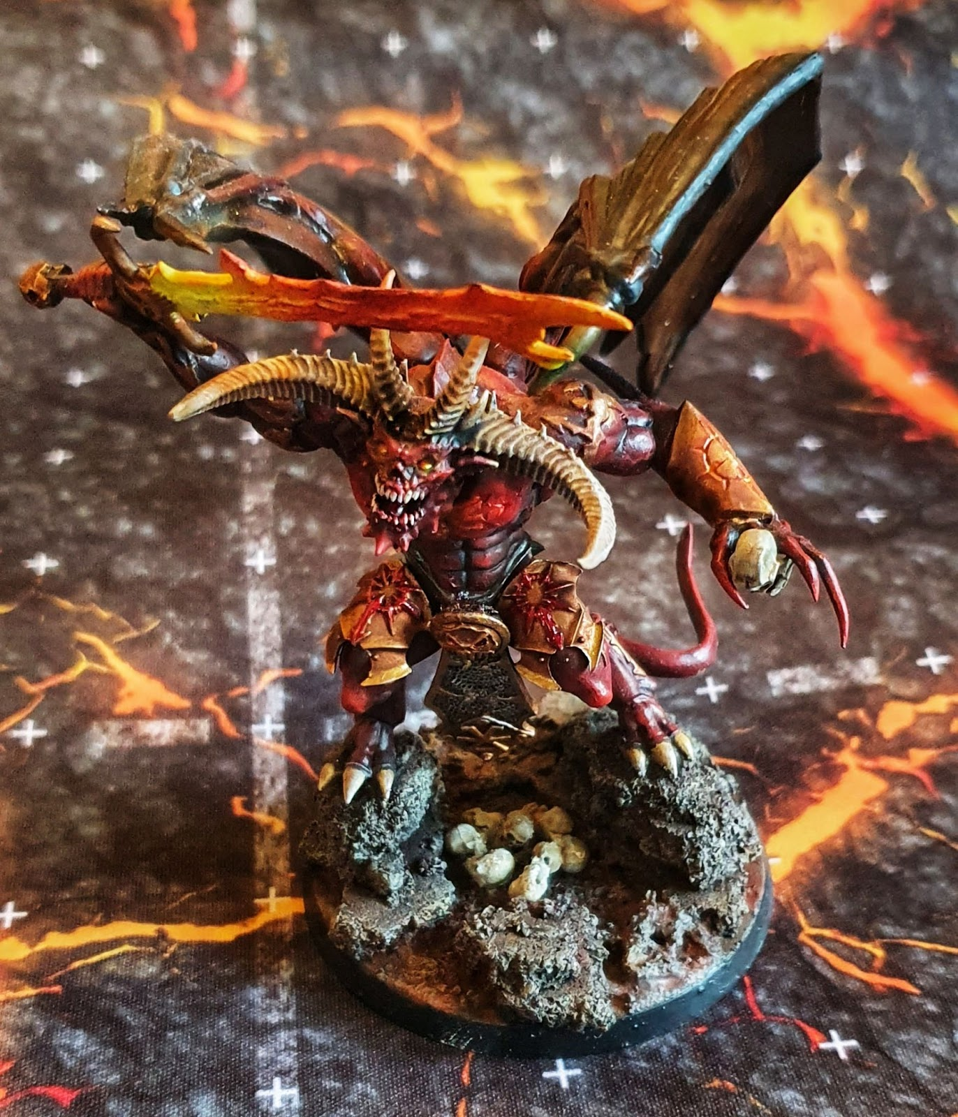 Demon Prince of Khorne model, holding a skull in one hand, with a lava sword and gold armour.