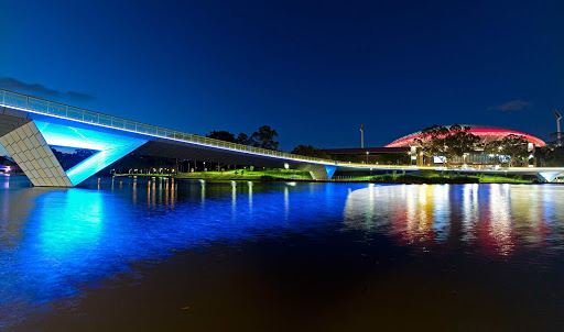 Torrens-River-Adelaide-night - A footbridge across the Torrens River, with the Adelaide Oval stadium in the background, in South Australia.