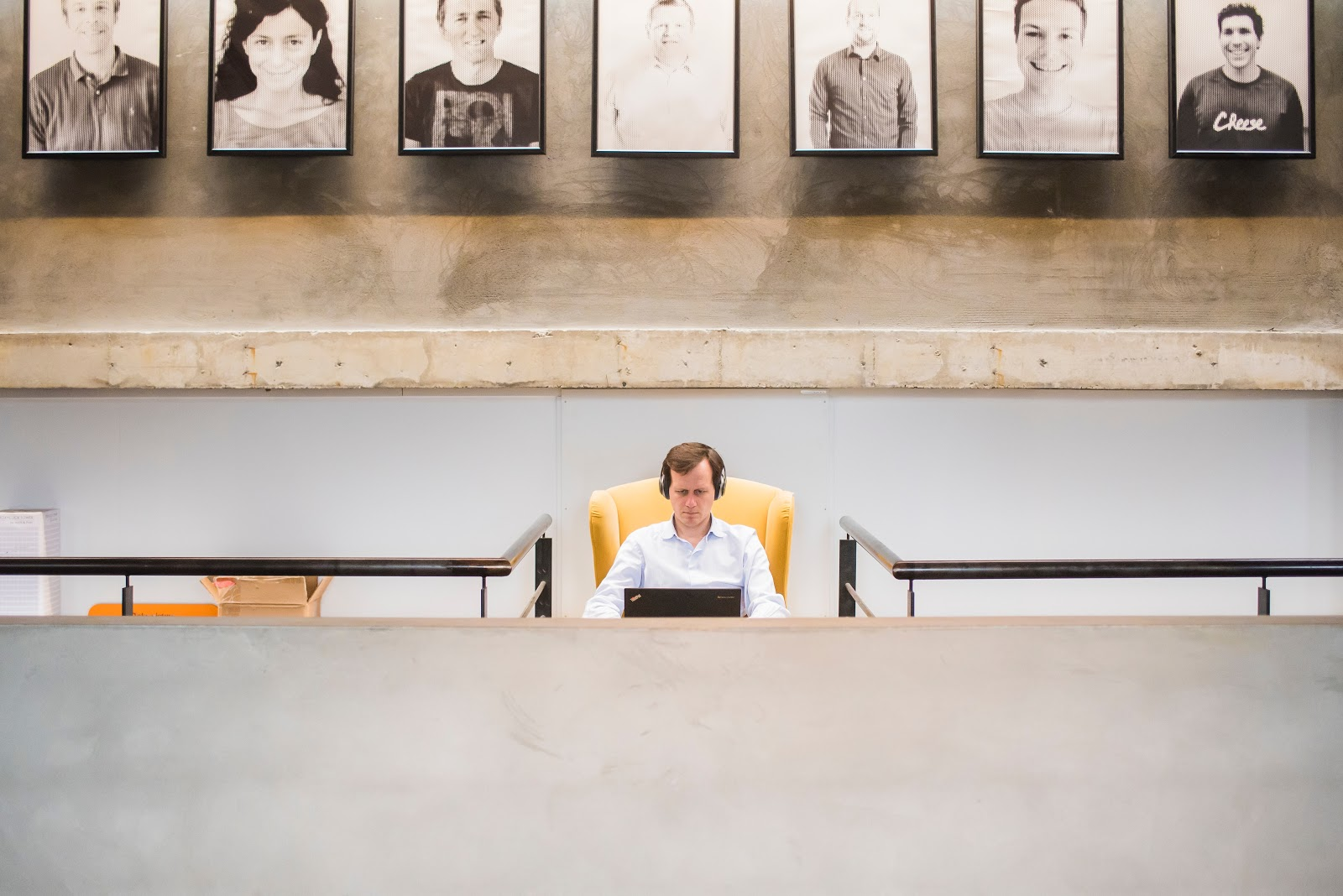 man alone at the table, pictures behind him. Helpdesk center