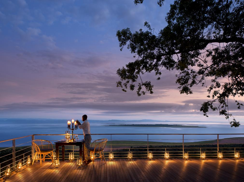 A person lighting candles with the amazing views of Lake Kariba in the background as sunsets