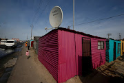A satellite dish connecting residents to the DSTV television network, owned by telecommunications giant Naspers, adorns a shack in Khayelitsha township, Cape Town, on May 25, 2017.