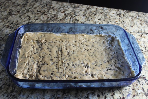 Press chocolate chip cookie dough into greased 9x13 dish. Bake as directed on package...