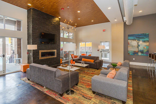 Community clubhouse with modern light fixture, dark stone fireplace, and modern plush lounge seating