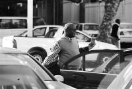 SMILING:Advocate Letsepe Thubakgale was suspended for 60 days by Polokwane Municipality as a Municipal Manager. Sowetan photographer took  a picture of him leaving  his office on his first day after suspension. Pic: ELIJAR MUSHIANA. 29/07/2009. © Sowetan