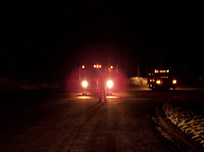 Photo: Firefighter barely visible in the glare of the lights of the apparatus. Even with just headlights on, a firefighter may be not be visible to oncoming vehicles.
