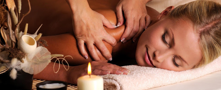 a blonde lady receiving a shoulder massage by candle light