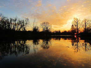 Photo: Fiery sunset reflected in a lake with dark, barren trees at Eastwood Park in Dayton, Ohio.