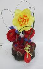 Photo: composition piquée dans de la mousse synthétique  fleurs utilisées: renoncules rouge, muscaris, et narcisses (joncquille) feuillage: beargrass  contenant fait artisanalement  prix: 12 euros