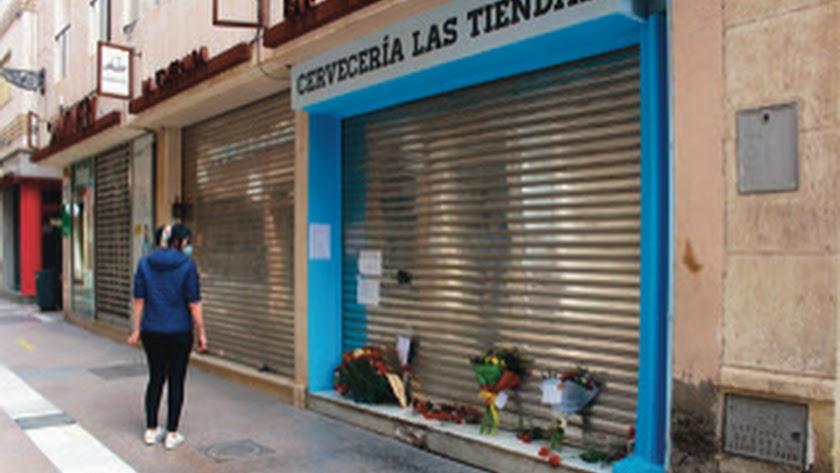 Muestra de cariño y flores en la puerta del bar.