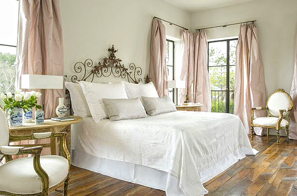 Elegant bedroom with French inspired decor, blush taffeta curtains, white bedding, and rustic wood floors. #pamelapierce #Frenchbedroom #FrenchCountry