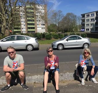 Drei Aktivisten des virtuellen Ostermarsch, hier ganz reell mit Ostermarsch-Flugis vor den Häusern in denen sie verteilt haben..