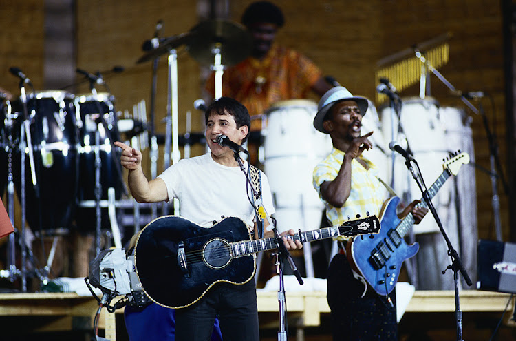 Paul Simon performs on stage with Ray Phiri during a tour to promote his Graceland album.
