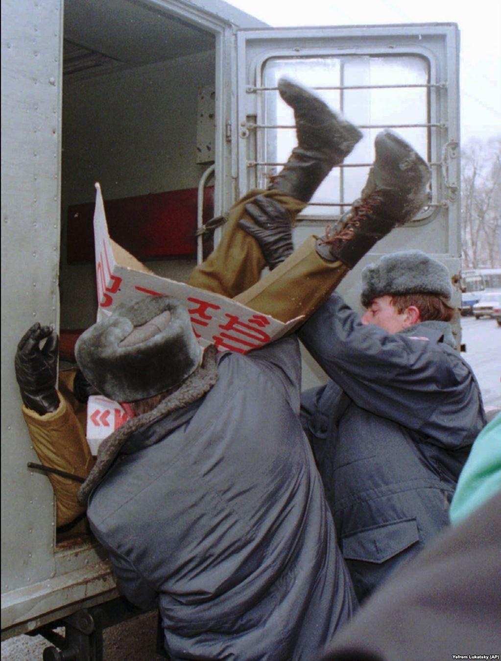 Міліція затримує учасника акції протесту в Києві 12 січня 1996 року. Кілька членів українського парламенту організували протест проти договору про без'ядерний статус України. У той час, коли міліціонери запихають його в міліцейський фургон, він тримає плакат із вимогою відставки тодішнього міністра оборони України Валерія Шмарова