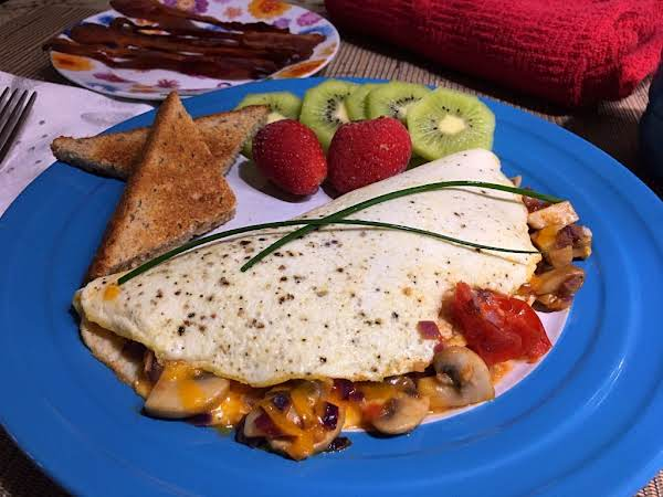 An Omelet Sitting On A Plate With Strawberries, Kiwifruit Slices And Toasts.