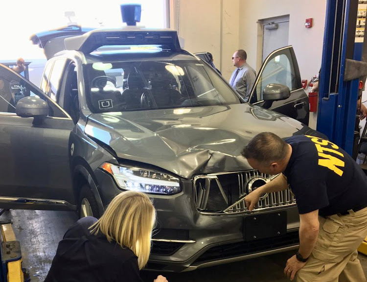FILE PHOTO: U.S. National Transportation Safety Board (NTSB) investigators examine a self-driving Uber vehicle involved in a fatal accident in Tempe, Arizona, U.S., March 20, 2018. Picture: National Transportation Safety Board/Handout via REUTERS