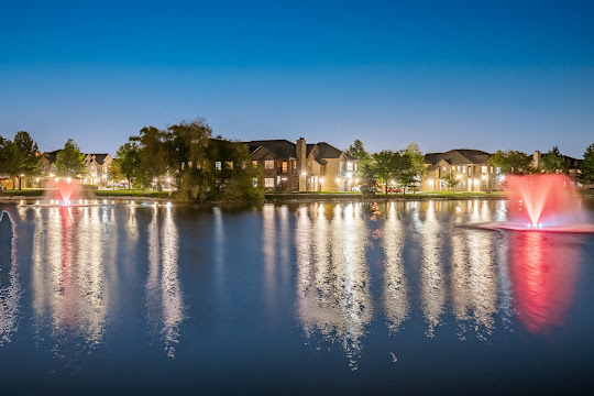 Village at Lionsgate's on-site lake with red fountains surrounded by lit up apartment buildings at night