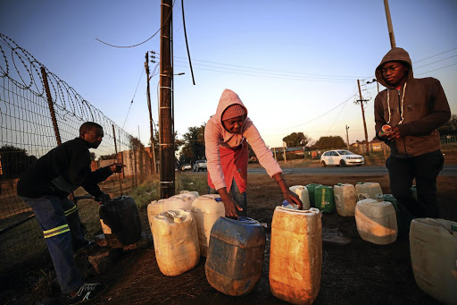 Men and women collect water in the early hours of the morning in Koster after the water was cut - in retaliation for service delivery protests, say some.