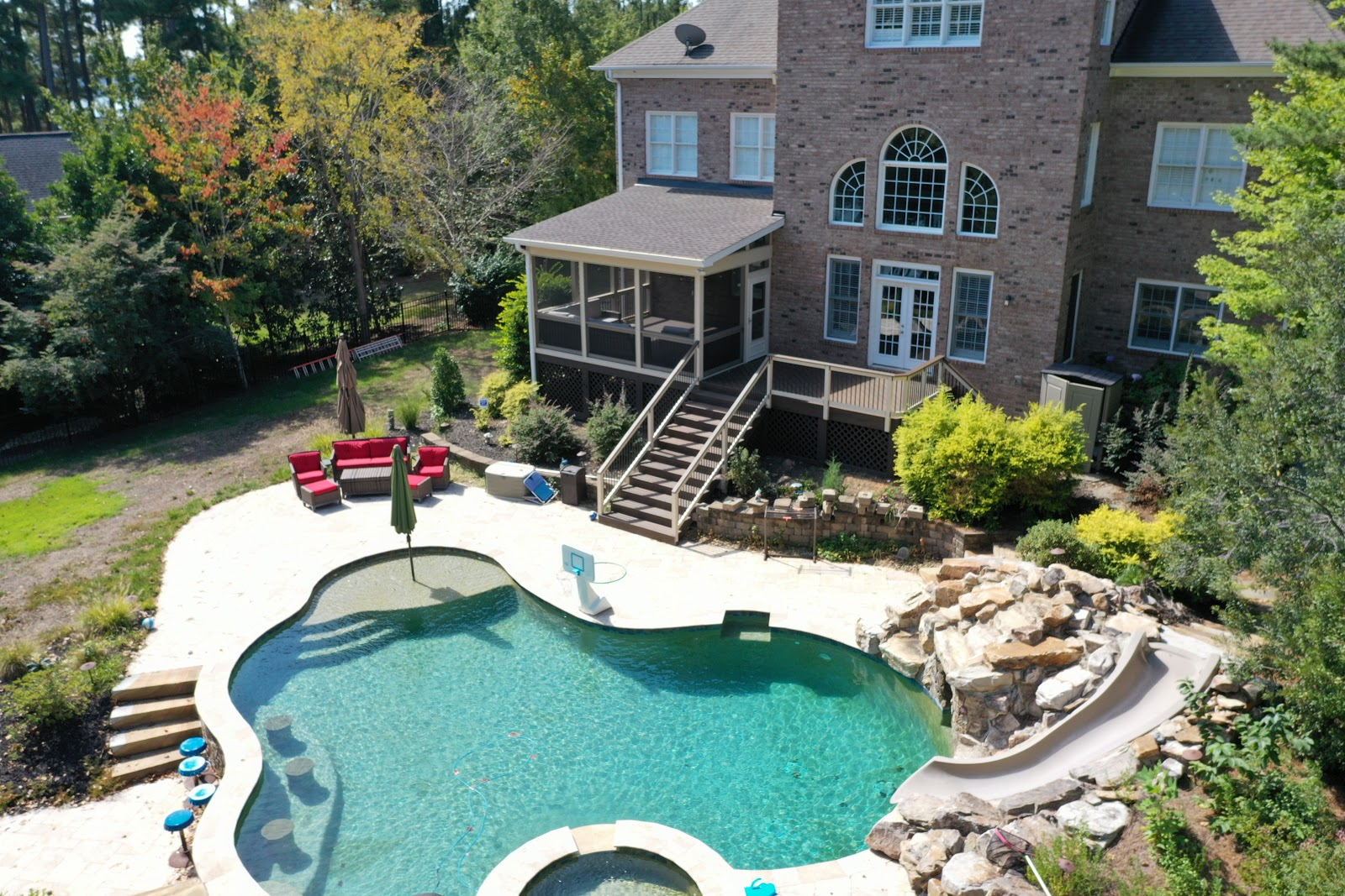 outdoor property overview with pool, covered porch, and stairs