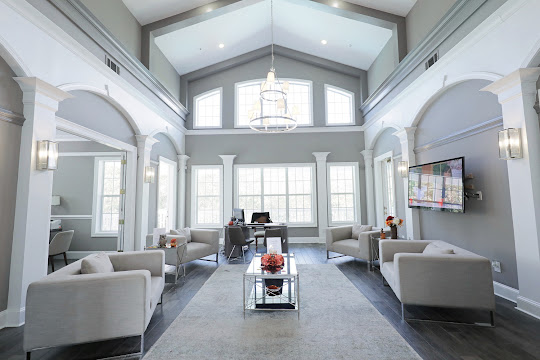 Community clubhouse with wood inspired floors, neutral colored walls, and seating area