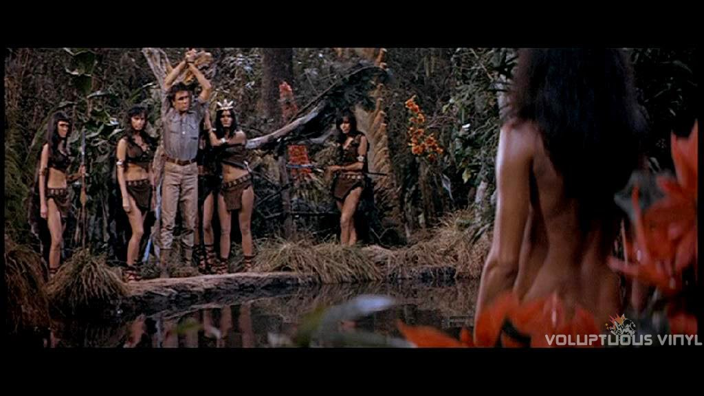 Captured by a tribe of bikini clad beauties, with leader Martine Beswick nude in the lagoon.