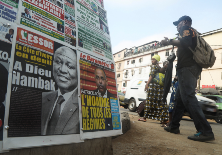 "People walk past a newspaper stand a day after the death of Ivory Coast's Prime Minister Hamed Bakayoko, in Abidjan, Ivory Coast on March 11, 2021. The newspaper title (L) reads ""Ivory Coast in mourning, Goodbye Hambak""."