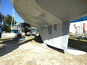Photo: Hanging in slings while repairing and fairing base of keel.  The single block has a slight amount of weigh on it to keep the boat from swinging while hanging in the slings.