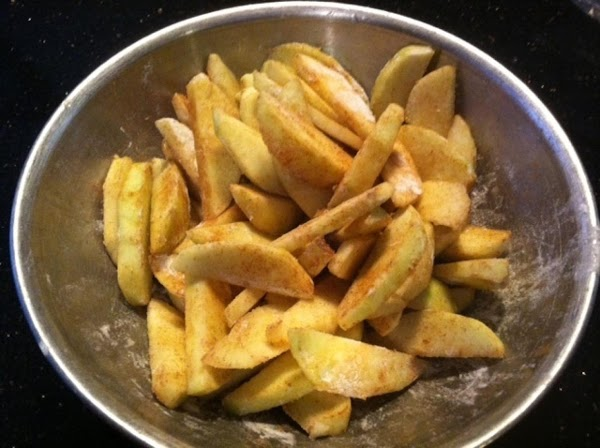 IN A MEDIUM BOWL COMBINE PEELED, SLICED APPLES WITH FLOUR, CINNAMON. MIX WELL.