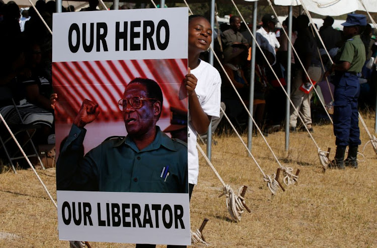 A mourner holds a poster as the body of former Zimbabwean president Robert Mugabe arrives in Murombedzi, near his rural home village of Kutama, Zimbabwe, on September 16 2019.