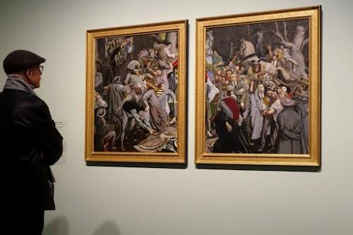 Ausstellungsbesucher betrachtet zwei Bilder.
