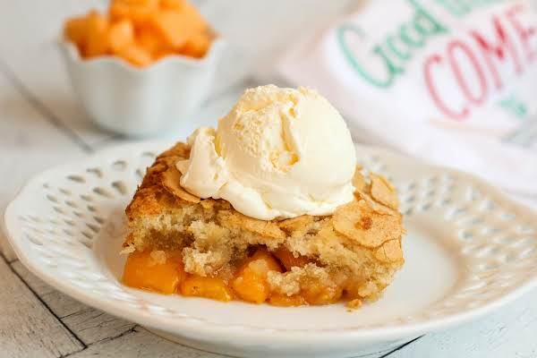A Slice Of Cantaloupe Peach Cobbler With Ice Cream.