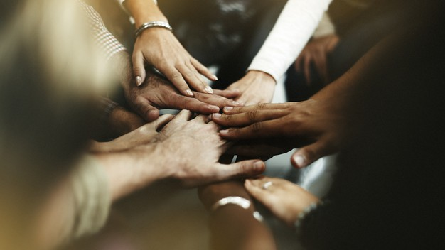 Closeup picture of diverse people joining their hands